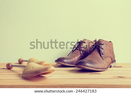 Still life with boots and wooden shoe tree on wooden table over grunge background   #246427183