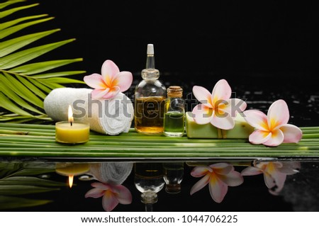 still life with bottle oil with frangipani ,soap,candle, rolled towel green plant
