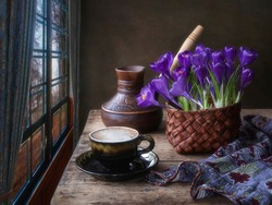 Still life with bouquet of purple crocuses and coffee cup