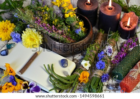 Still life with bowl of herbs, candles and old book on witch table. Esoteric, occult and mystic concept, alternative medicine background with natural ingredients.