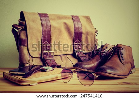 Still life with casual man, boots and bag on wooden table over grunge background #247541410
