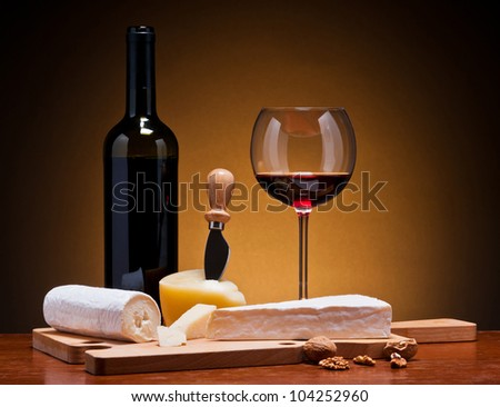 still life with cheese and red wine on a wooden table