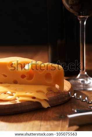Still life with cheese and wine in contrasting light