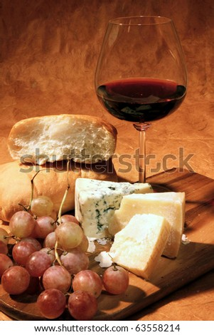 Still-life with cheese, grapes, italian ciabatta bread and glass of red wine.