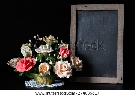 Still life with clay roses in basket with wood black board on wood background