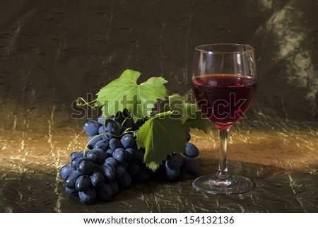 Still life with clusters of dark grapes and wine
