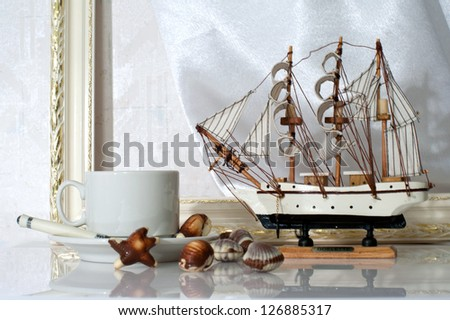 Still life with cup, candy, souvenir yacht and frame molding