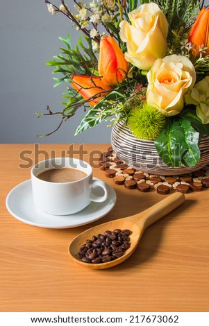 still life with cup of coffee and flower on wooden table