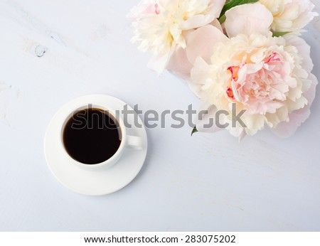 Still life with cup of coffee and flowers (peonies) on light blue wooden table.