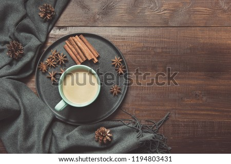 Still life with cup of coffee, warm scarf on wooden board. Copy space. View from above.
