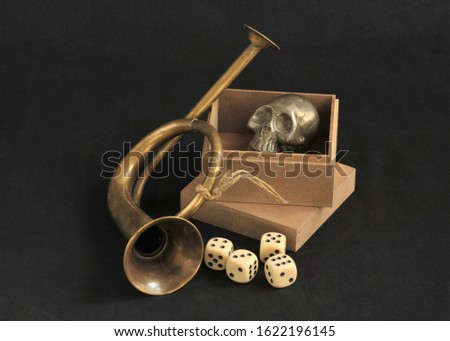 Still life with dices, brass toy trupet and silver scull