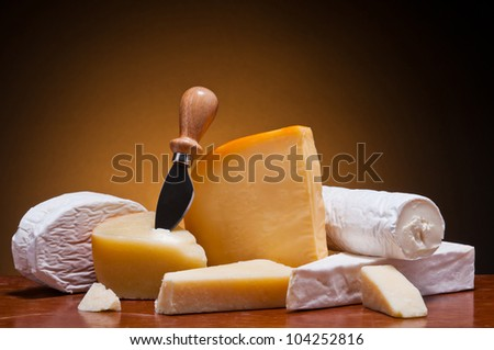 still life with different cheese on a wooden table