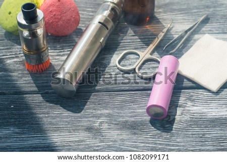 Still life with e-cig and jiuce on the wooden background #1082099171