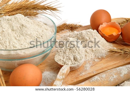 Still life with flour and eggs on a wooden board