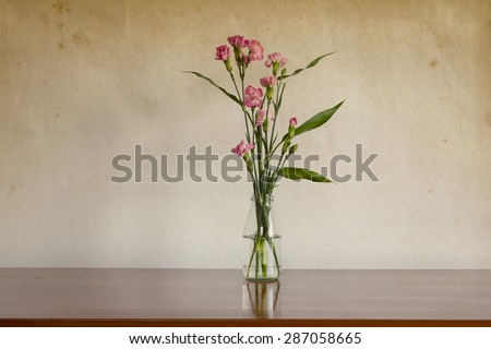 Still life with flowers in glass bottle on wooden table