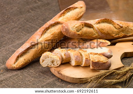 still life with French fresh bread baguettes with poolish on a wooden cutting board and wheat, shallow dof