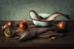 still life with fresh fish with onion and lemon
