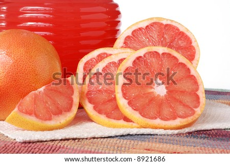 Still-life with freshly sliced and whole red grapefruits.  Glass decanter filled with ruby red grapefruit juice in the background.
