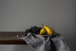 Still life with fruits. Grapes and pears on a rustic table indoors with a moody window light