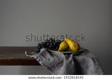 Still life with fruits. Grapes and pears on a rustic table indoors with a moody window light 商業照片 ©