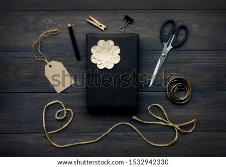 still life with gift box wrapped in black paper and the contents of a workspace composed. #1532942330