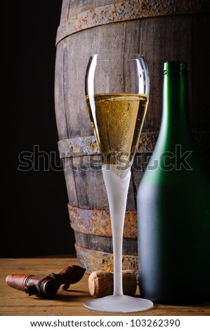 Still life with glass and bottle of champagne or prosecco in cellar with wooden barrel