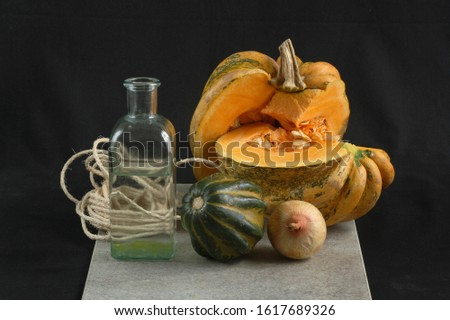 Still life with glass bottle, pumpkins and onion