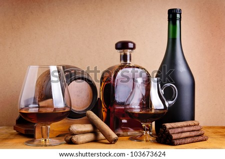 still life with glass, bottles and barrel of cognac with cigars on wooden background