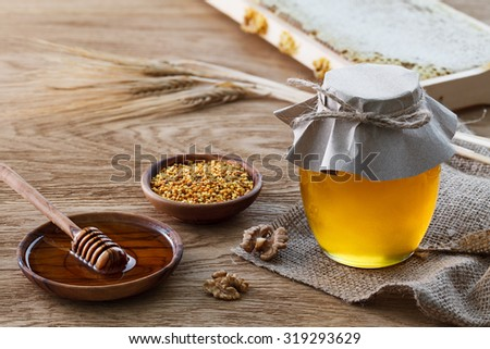 Still life with glass jar full of honey, tee bowl with bee pollen, honeycombs frame, walnuts and rye ears.