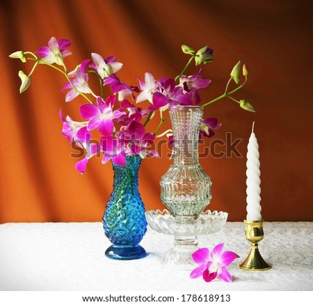still life with glass,vase,orchid,glass tray with pedestal and candle.