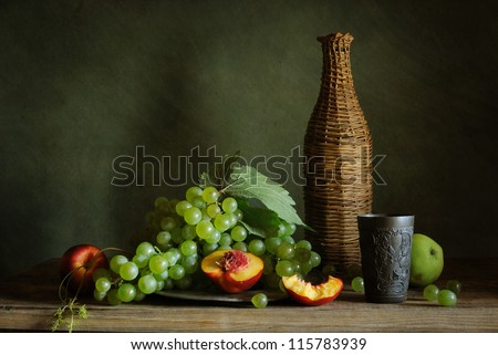 Still life with grapes and a tin cup