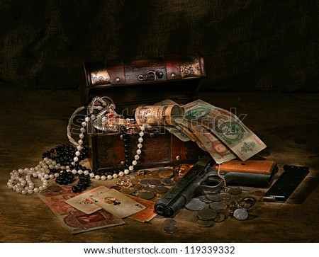 Still life with gun, money,treasures,cards in box on a dark background