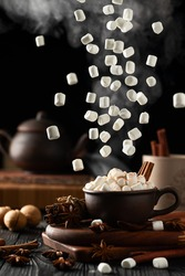 Still life with hot chocolate and marshmallows. Marshmallow falls from above. Hot steam rises from the mug