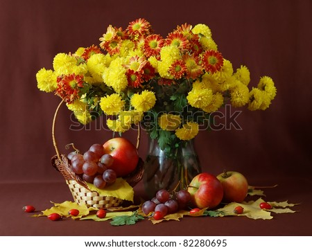 Still life with huge bunch of autumn flowers, grapes, red apples and hips