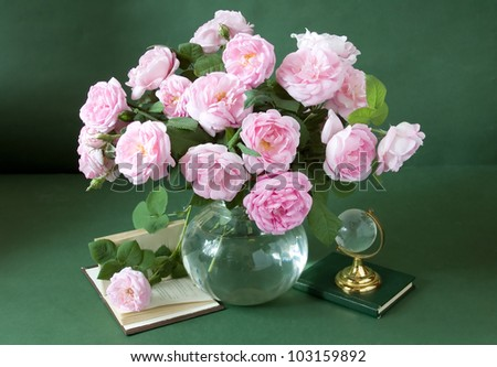 Still life with huge bunch of pink roses, books and globe on painting background