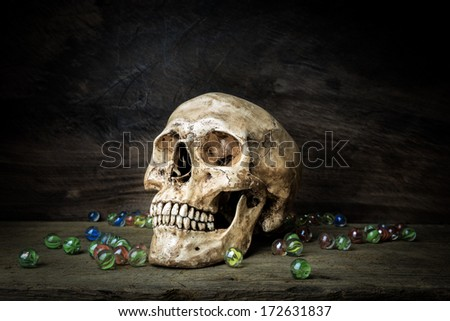 Still life with human skull and crystal ball on wooden table