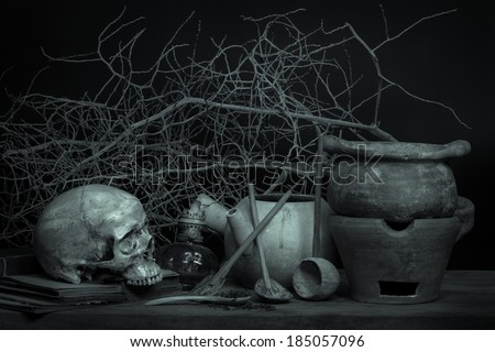 Still life with human skull on old books and clay pots