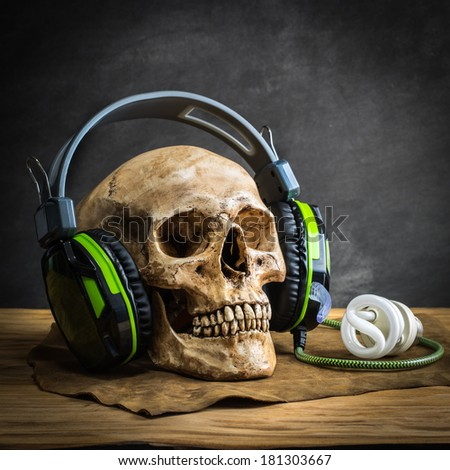 Still life with human skull wearing headphones