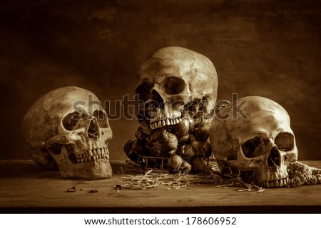 Still life with human skulls and bunch of garlics on wooden table
