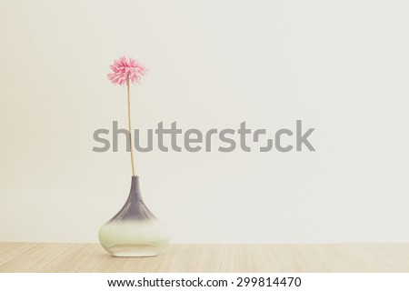 still life with jug and pink flower on the top of wooden table