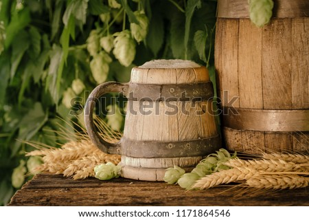 Still Life with keg of beer and draft beer in the ancient wooden mug on rustic table in front of hop plantation.