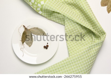 Still Life with laurel leaves and bell pepper on a white plate on a background of green towel