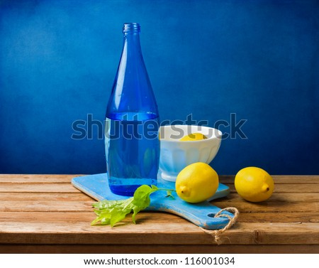 Still life with lemons and blue bottle on wooden table over grunge blue wall