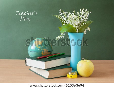 Still life with lily of valley bunch, books pile, apple and pencils on blackboard. Teacher\'s day concept