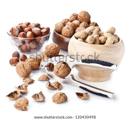 Still life with nuts and nutcracker on white background