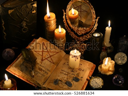 Still life with old book, ancient runes and mirror in candle light. Halloween and occult concept, black magic ritual. There is no foreign text in the image, all symbols are imaginary and fantasy ones  #526881634