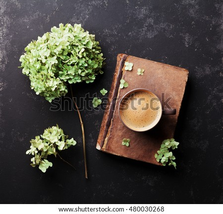 Still life with old book, coffee and dried flowers hydrangea on black vintage table top view. Flat lay styling.