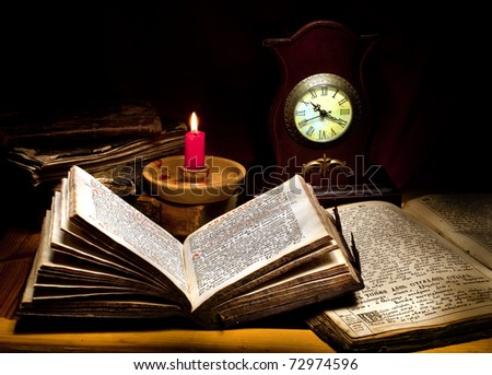 still life with old books, candle and clock
