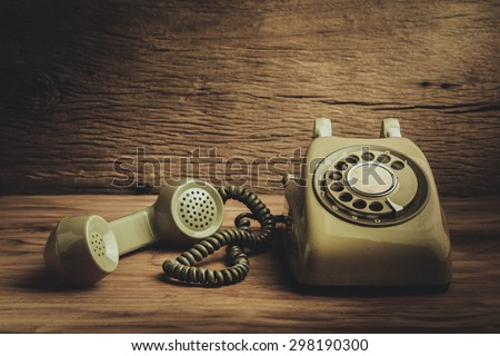 Still life with old green telephone on wooden table