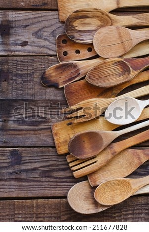 Still life with old wooden kitchen accessories, onions and bread onto an vintage surface. Kitchen wooden utensil of scapula, spoon and fork on wooden table. Natural old food concept . Top view.